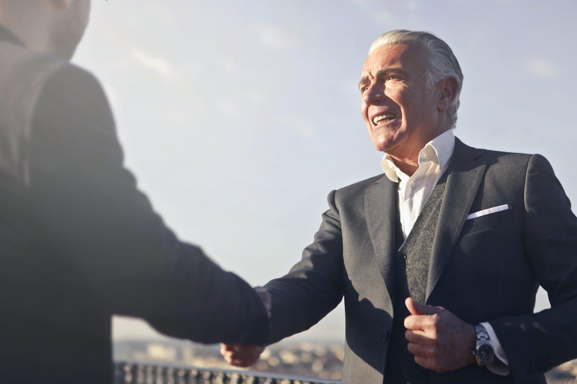 黑色西裝的男人與另一個男人握手
