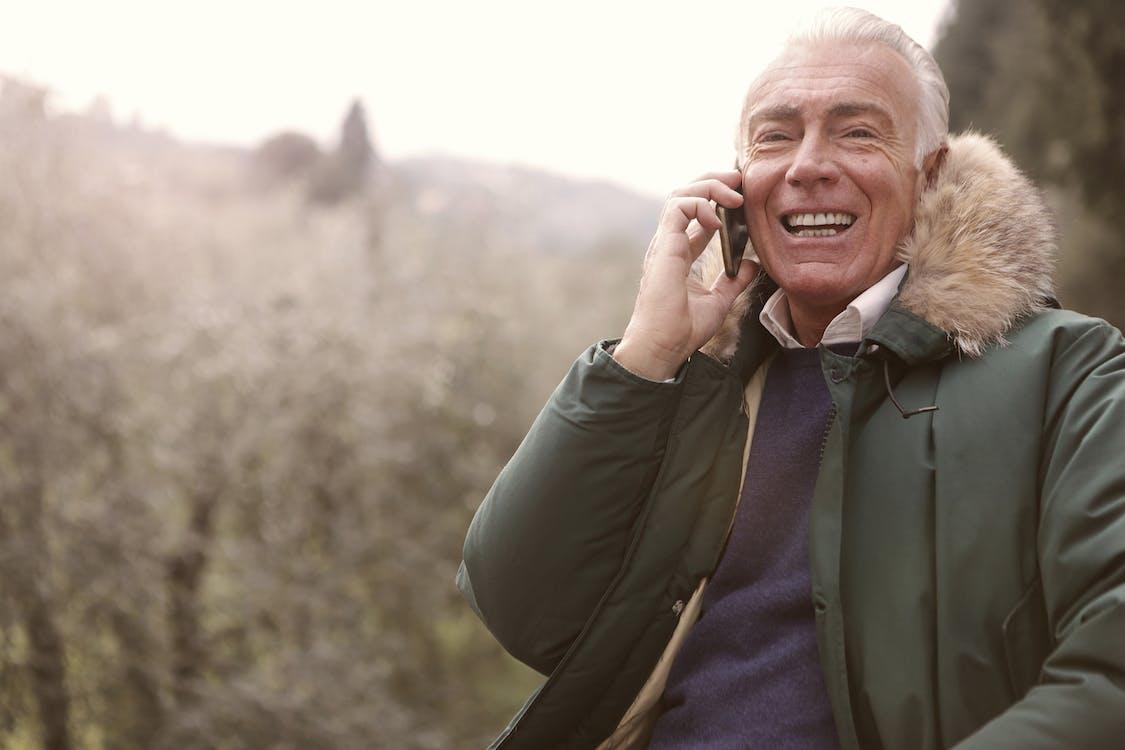 Man Wearing Gray Coat Using a Cellphone
