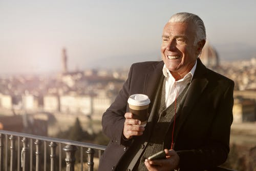 Man In Black Suit Holding A Coffee Cup