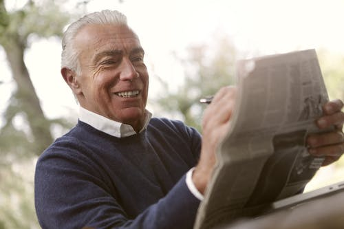 Smiling Man In Navy Blue Sweater Holding A Newspaper