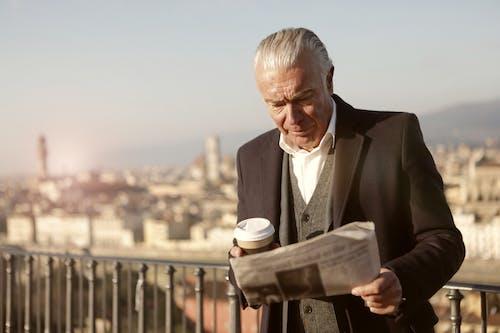 Man In Black Suit Reading Newspaper