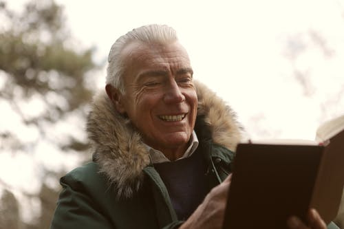 Man In Green Jacket Smiling While Reading