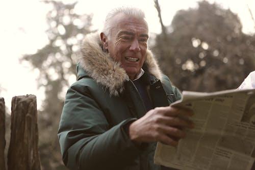 Uomo In Giacca Verde In Possesso Di Un Giornale