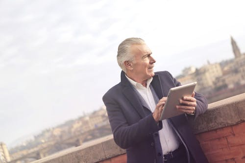 Man In Black Suit Holding A Tablet