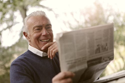 Man In Navy Blue Sweater Holding Newspaper