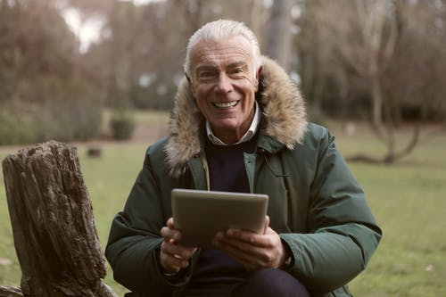 Adult Man Wearing Green Jacket Holding a Tablet