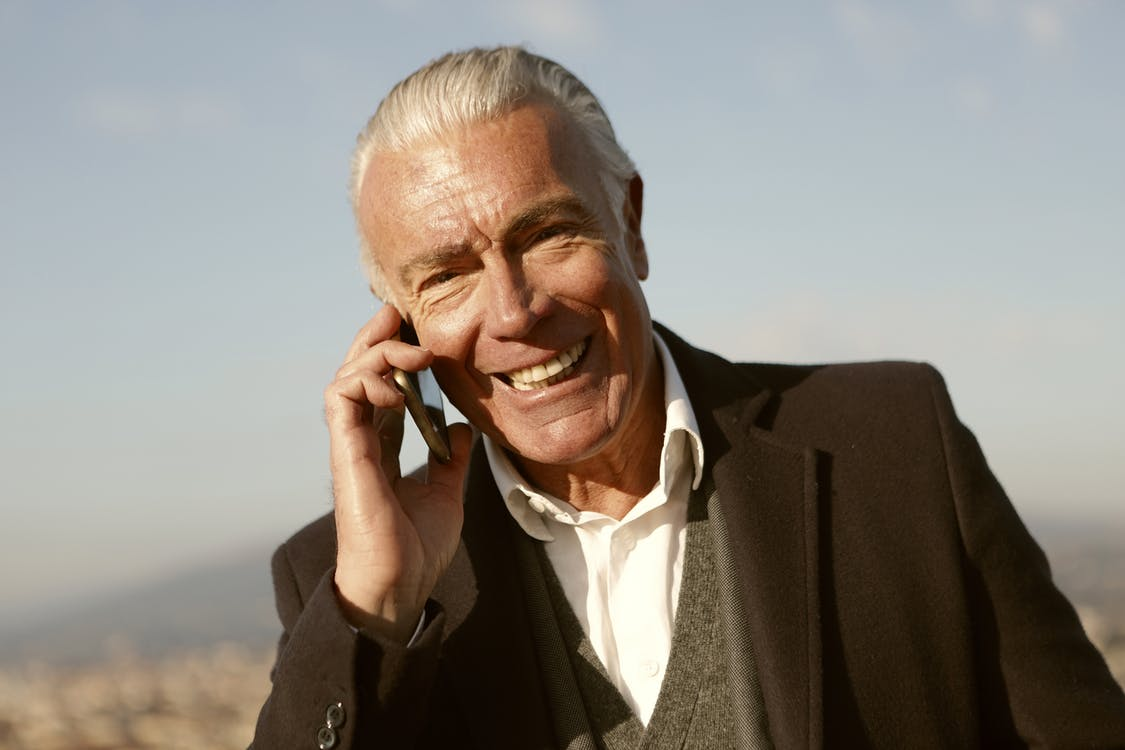 Man in Black Suit Using A Cellphone