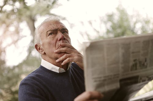 Man in Blue Sweater Reading a Newspaper
