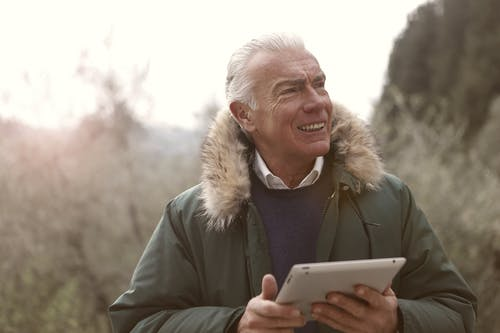 Man in Green Jacket Holding Silver Ipad