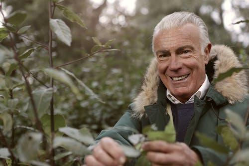 Homem Com Casaco Verde Em Pé Perto Da árvore De Folhas Verdes