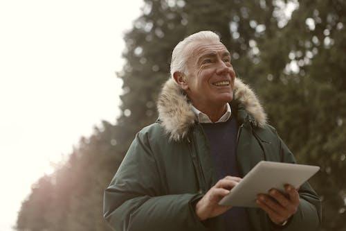 Homem De Jaqueta Verde Segurando Um Computador Tablet Branco
