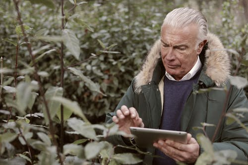 Man in Green Coat Holding Tablet
