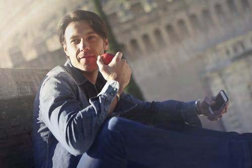 Young Man In Denim Jacket Holding Red Apple and Mobile Phone