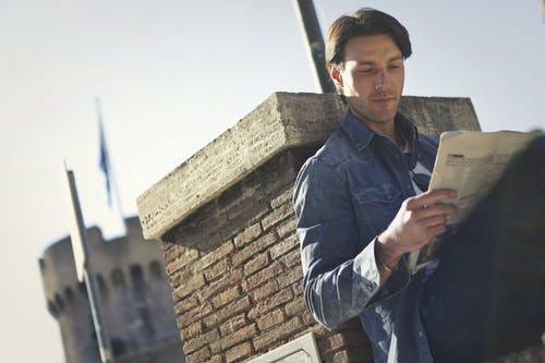 Man In Denim Jacket Holding A Newspaper