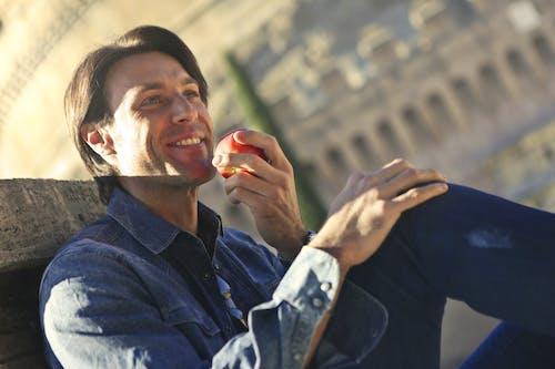 Man In Blue Denim Jacket Holding A Red Apple