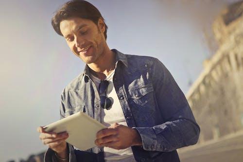 Man In Blue Denim Jacket Holding A Gadget