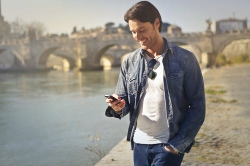 Man In Denim Jacket Holding A Smartphone Standing Near The River