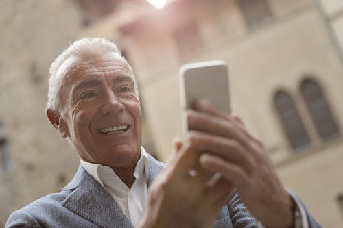 Elderly Man Using Smart Phone To Communicate To His Family