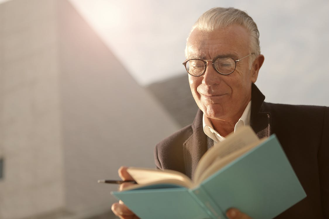 Man In Black Suit Reading A Book