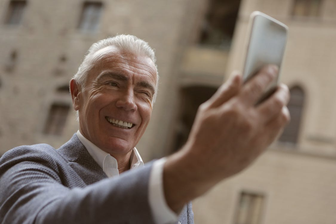 Man In Gray Suit Holding A Mobile Phone