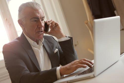 Man In Black Suit Using Laptop