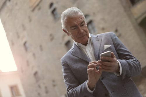 Man In Gray Suit Holding A Smartphone