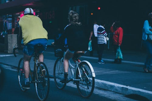 Two Person Riding on Bicycle Beside Sidewalk