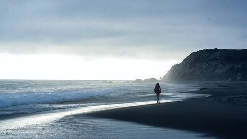 Silhouette Photo of a Woman Walking on Seashore