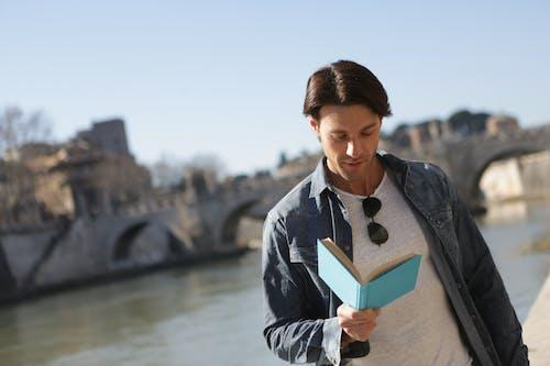 Man in Blue Denim Jacket Holding Book