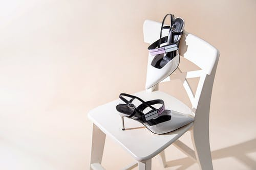 Black and White Leather Peep Toe Heeled Sandals on White Table