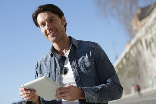 Man in Blue Denim Shirt Holding White Tablet