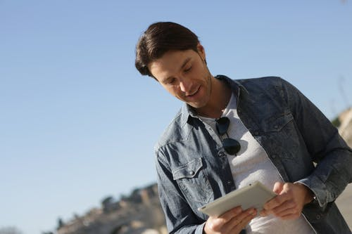 Man in Blue Button Up Shirt Holding White Tablet