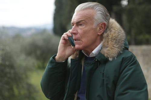Man in Green Jacket Holding Phone