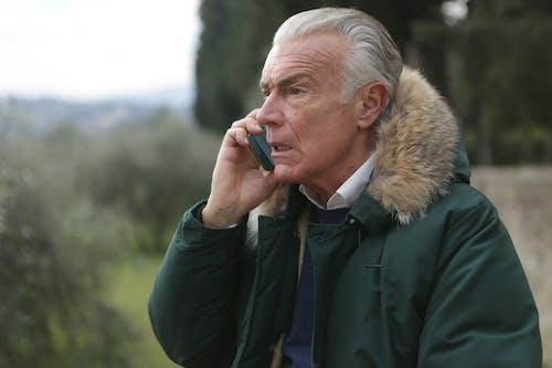 拿著電話的綠色夾克的人