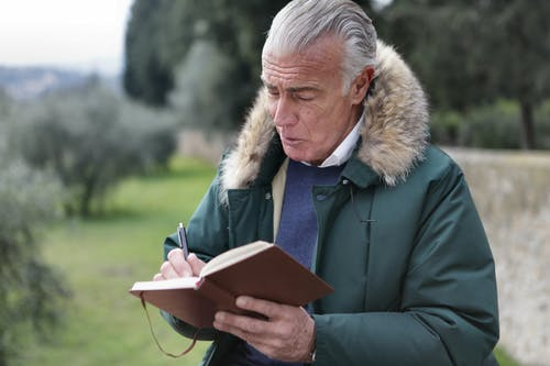Man in Green Jacket Holding Brown Book and a Pen