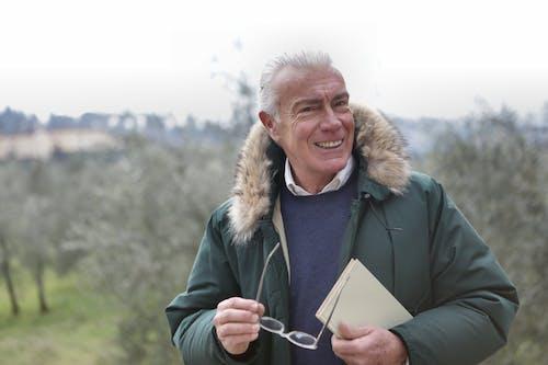 Hombre En Chaqueta Verde Y Gafas Sosteniendo Libro