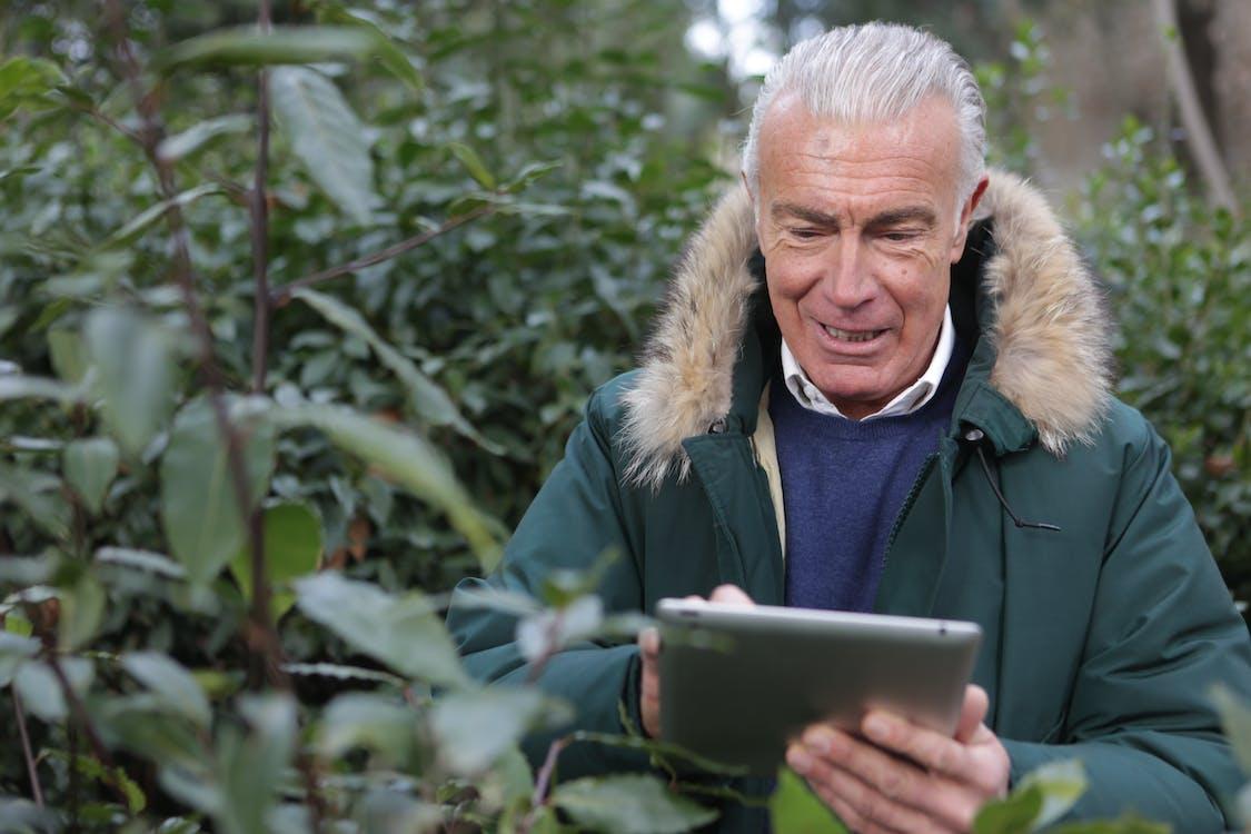 Homem De Jaqueta Verde Segurando Um Tablet Prateado