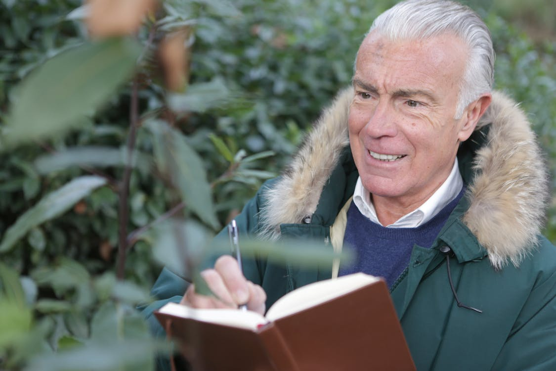 Man in Green Jacket Holding Brown Book and Pen
