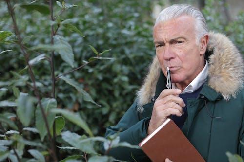 Hombre De Chaqueta Verde Con Lápiz Y Libro Marrón
