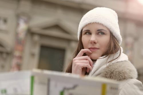 Concentrated female in warm hat and coat looking for right way while standing with map in street