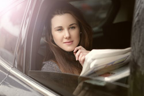 Young woman with newspaper in car