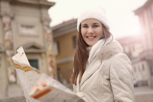 Young female tourist in warm jacket hat and scarf holding paper map and looking at camera while standing in historical center of city