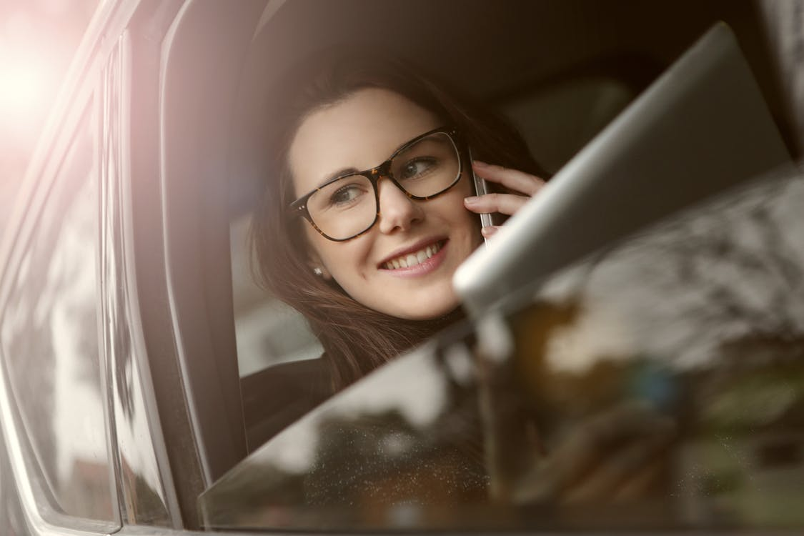 Female in glasses with tablet talking on smartphone while sitting in car with opened window