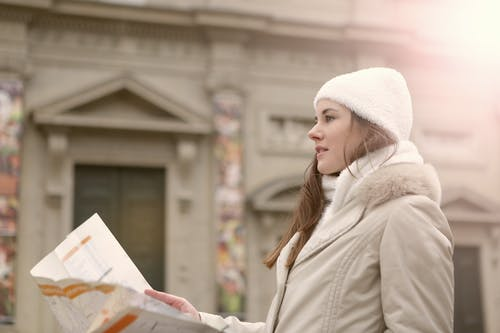 Young woman reading paper map in street