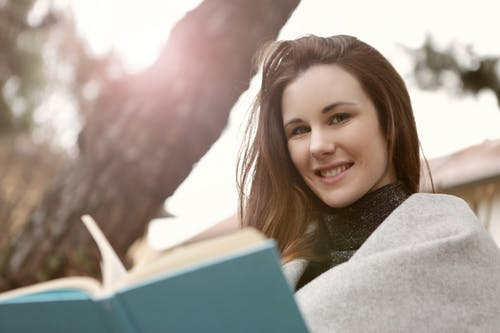 Positive woman reading book in city park
