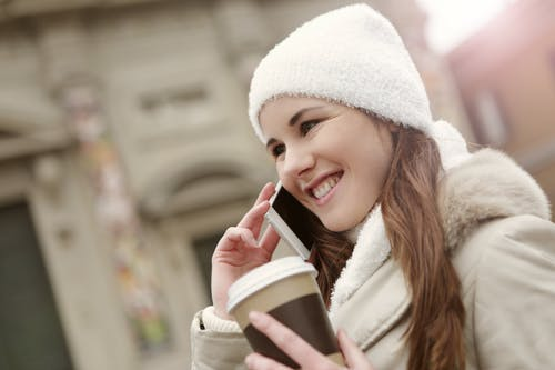 Charming woman with takeaway coffee speaking on smartphone in city