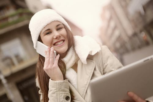 談話在智能手機和在街道上的使用片劑的美滿的婦女