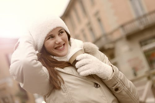 Smiling Woman in White Coat Wearing White Knitted Gloves