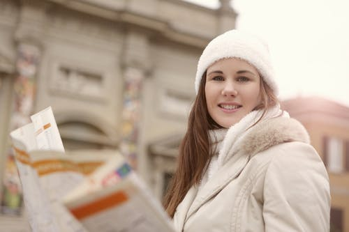 Young Woman in White Fur Coat Holding  a Road Map