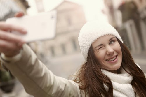 A Tourist Woman in White Knitted Bonnet Taking Selfie